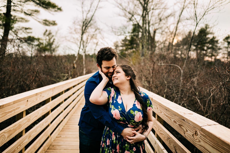 Couple hugging on boardwalk in Norwalk, Massachusetts