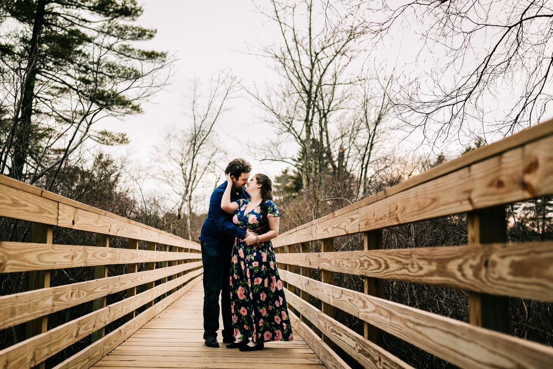 Couple on bridge over lake near Boston Massachusetts wearing blue floral dress