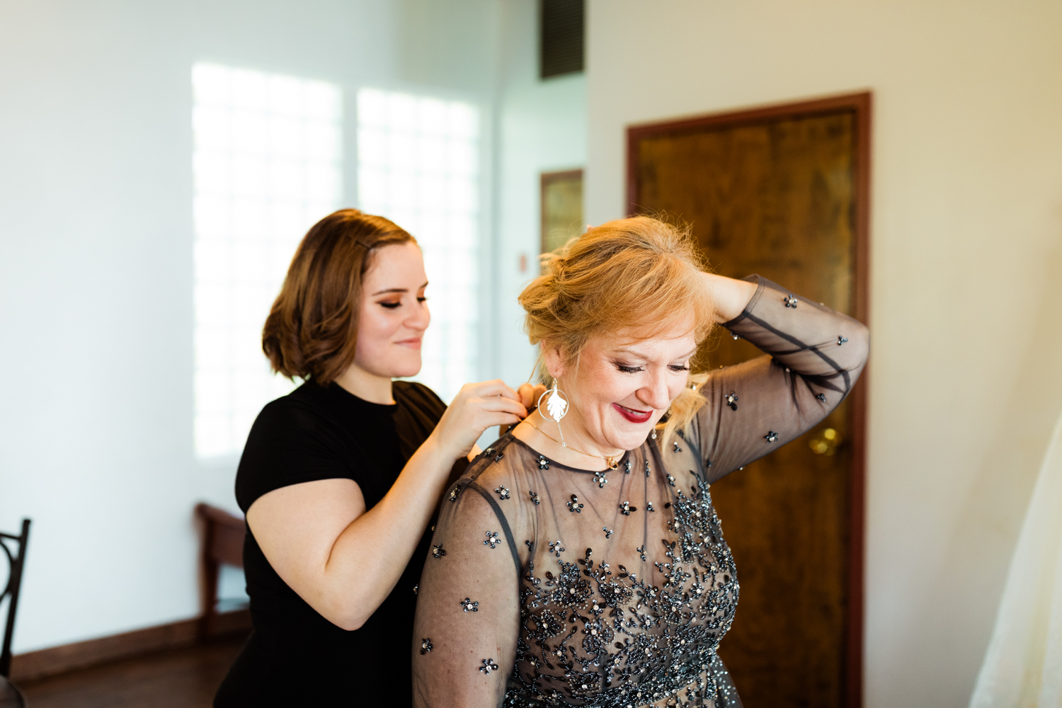 Mother of the bride putting on necklace on wedding day