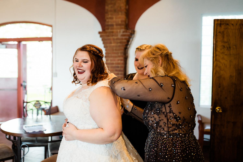 Laughing bride putting on wedding dress