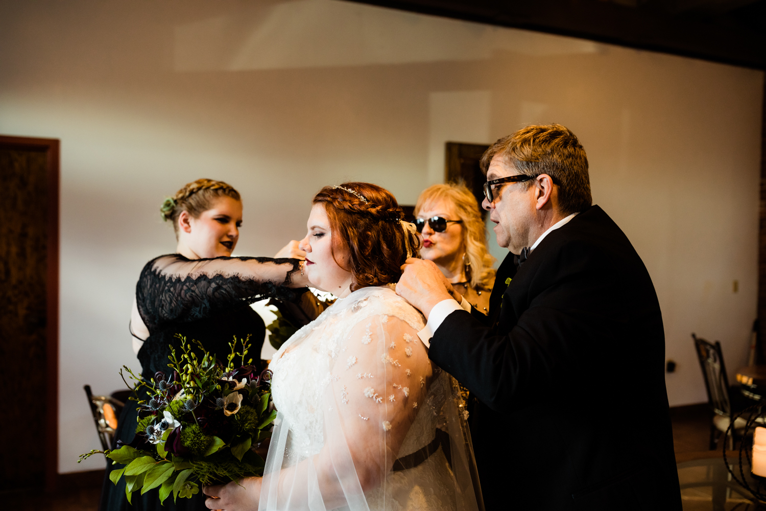 Cape-wearing bride's family helping put on pearl necklace on wedding day