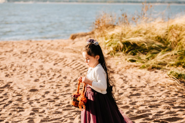 Flower girl wearing purple skirt on beach wedding