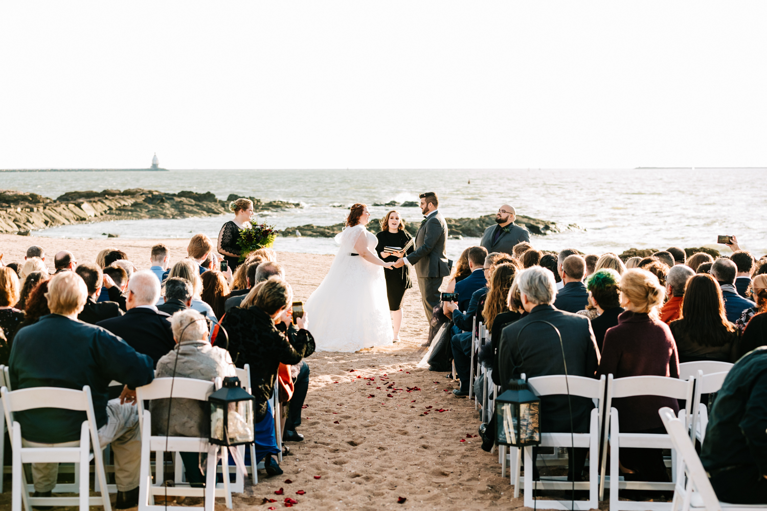 Guests watching bride and groom's ceremony on beach