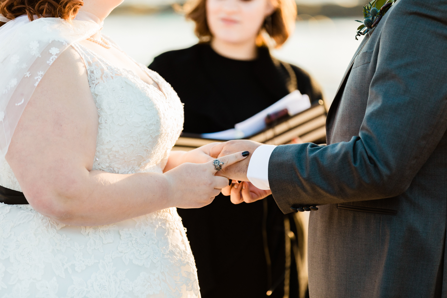 Bride wearing wolf ring exchanging wedding rings at beach ceremony