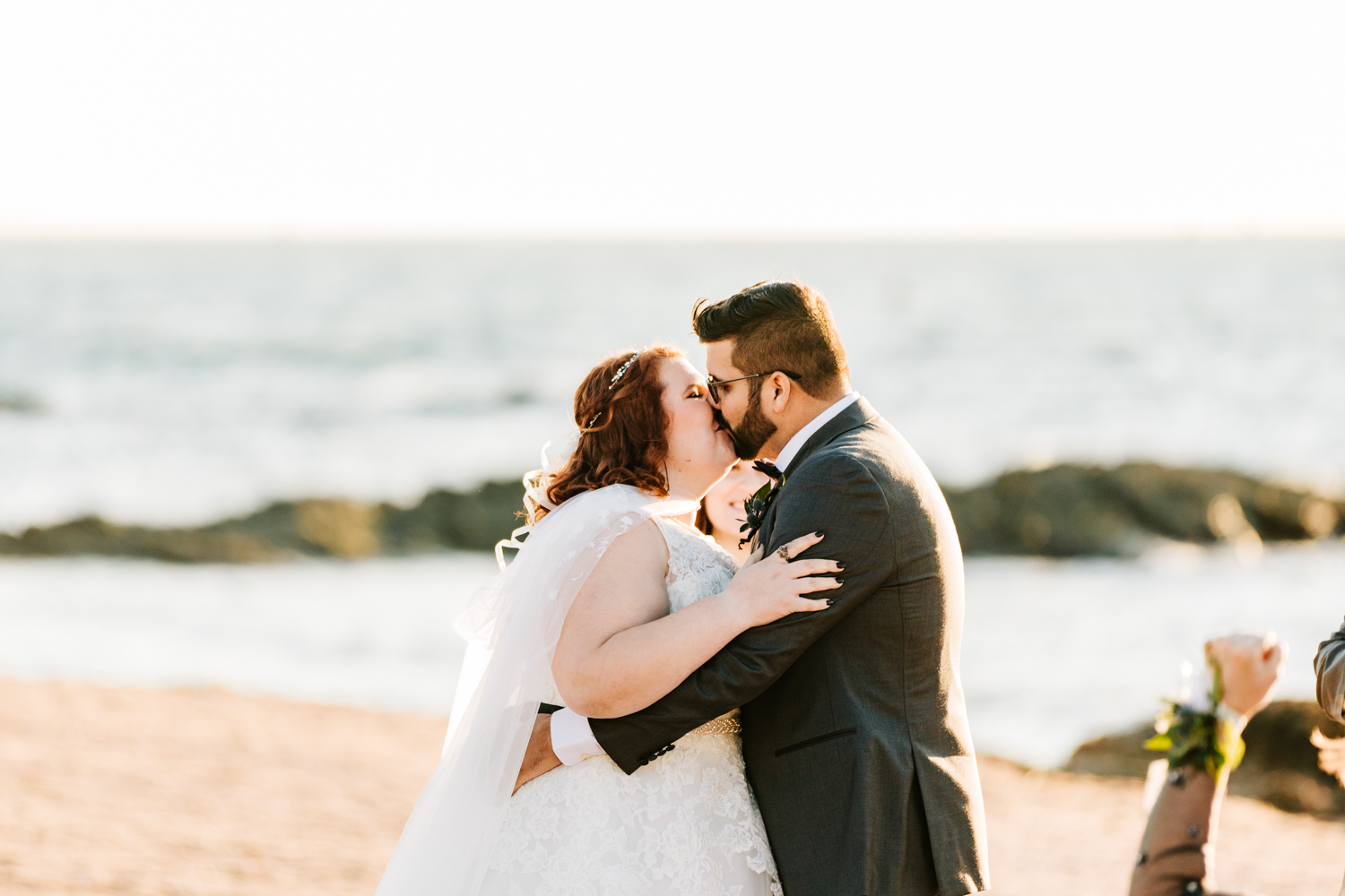 cape wearing bride and groom first kiss on beach wedding ceremony