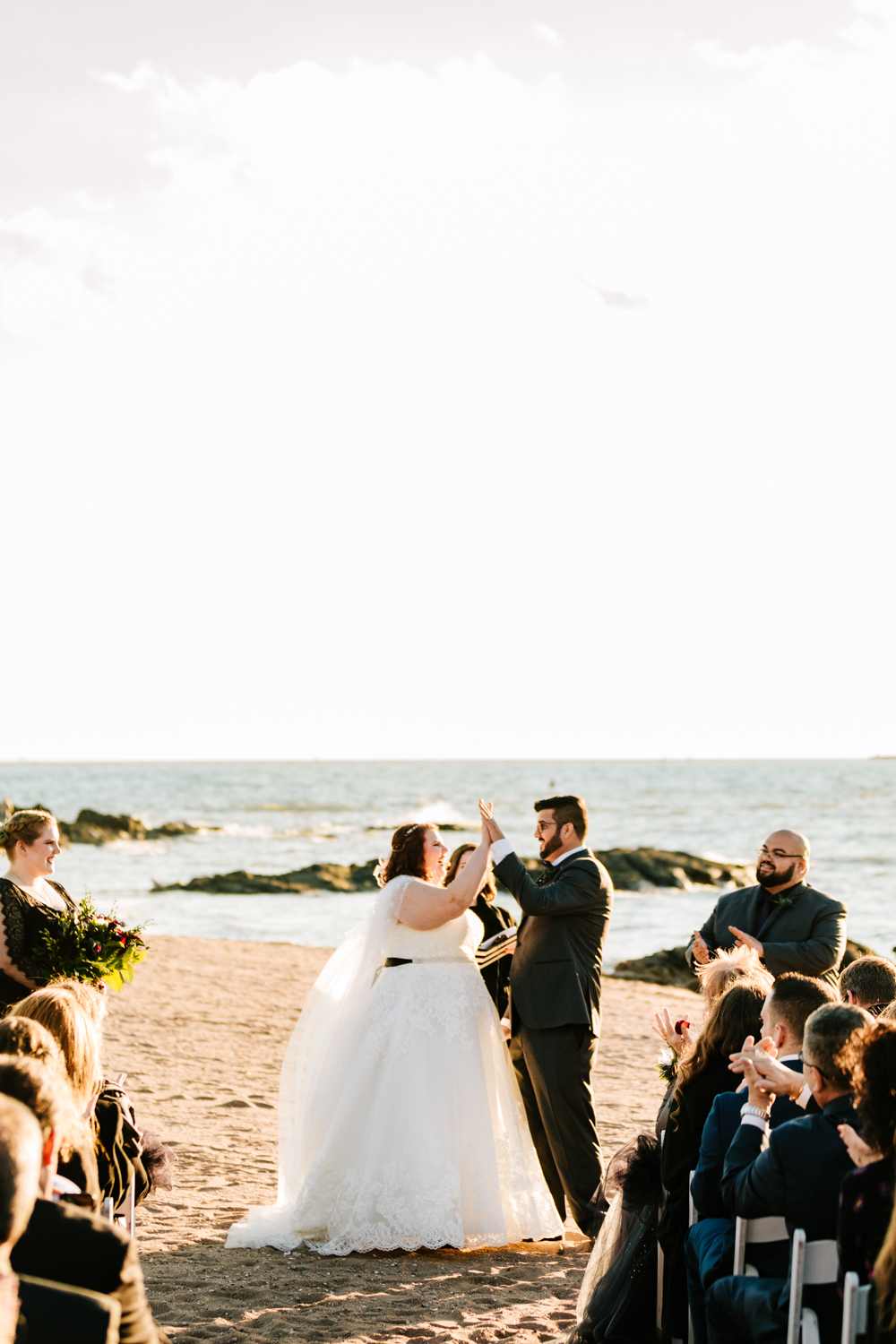 Bride and groom high five on beach ceremony