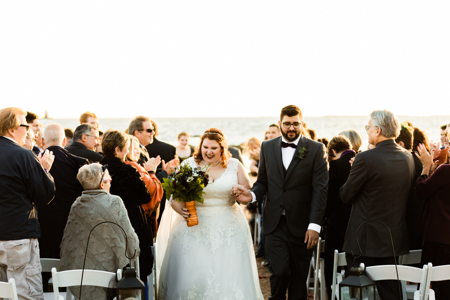 Bride and groom walking down aisle on beach wedding ceremony