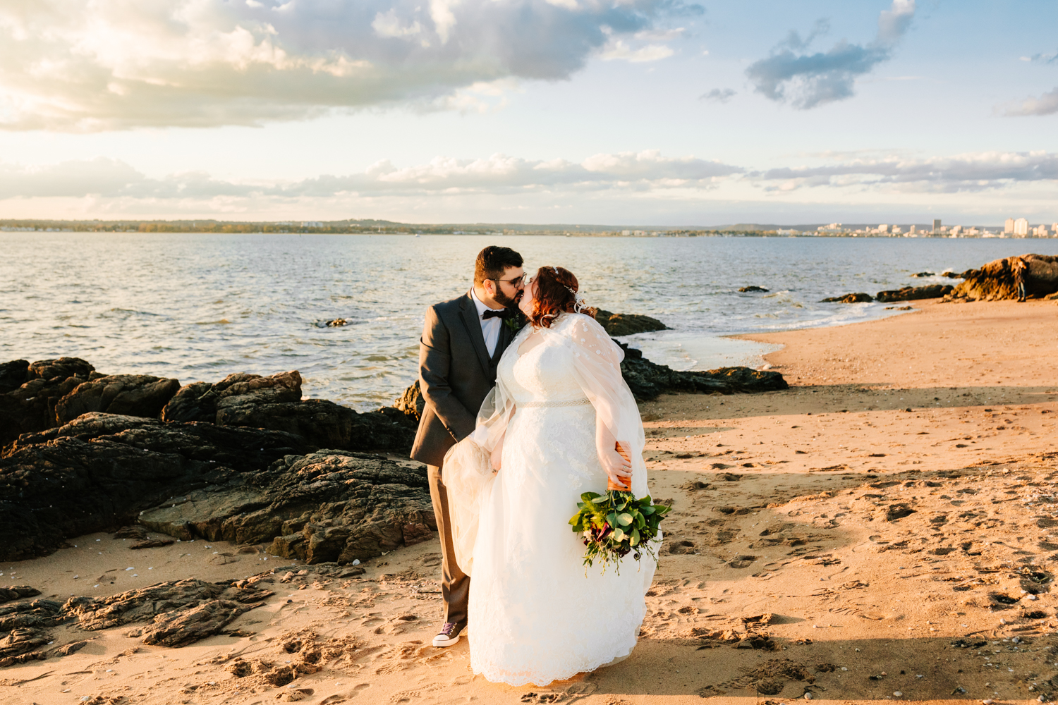 Bride and groom kiss on beach during sunset