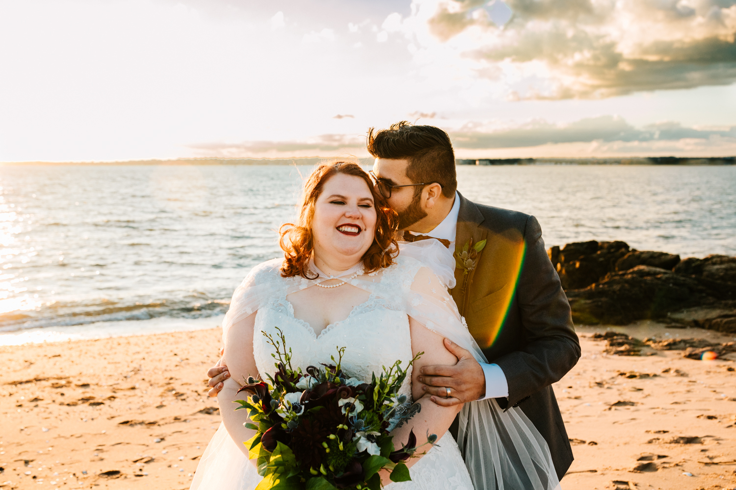 Red haired bride holding bouquet kissed by groom on beach