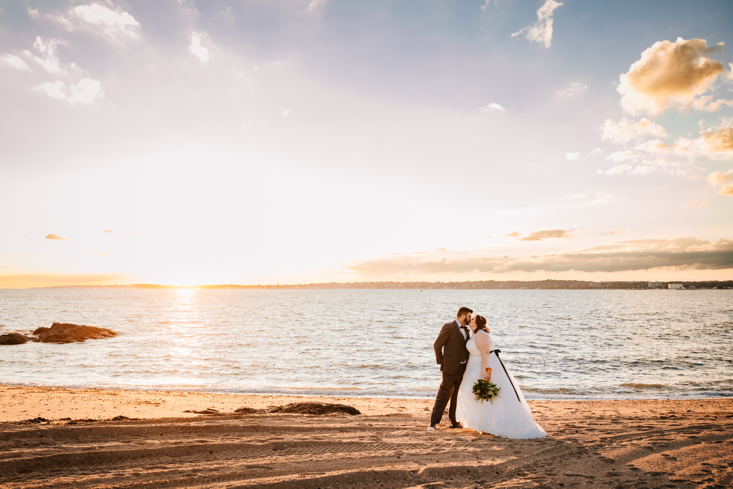 Landscape bride and groom at ocean at sunset