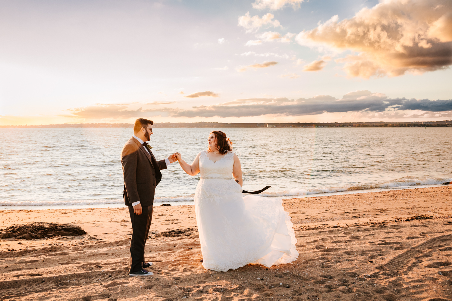 Bride and groom dancing on beach during sunset wedding day