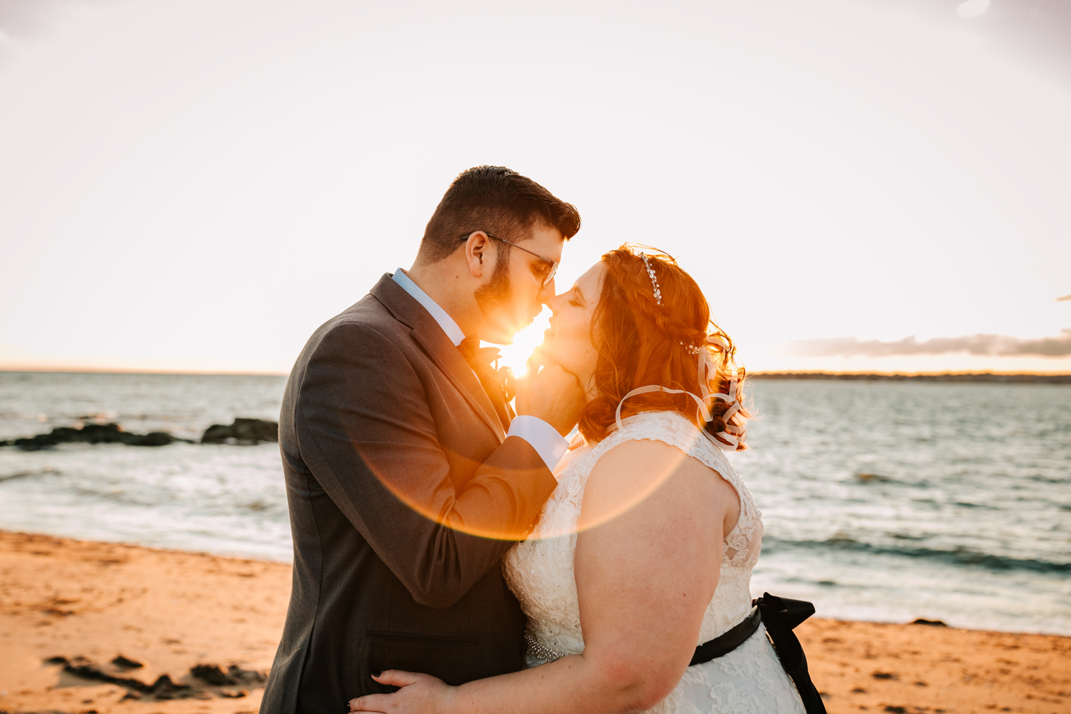 Sunflare with bride and groom kissing on sea wedding