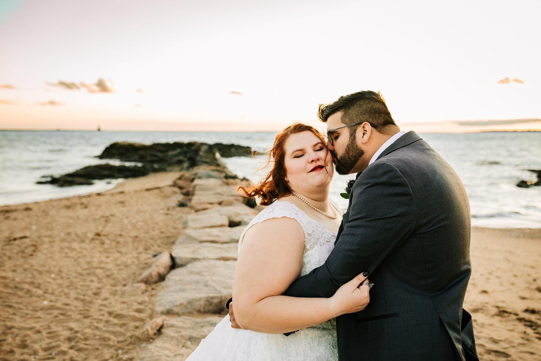 Groom kissing bride on rocks at ocean wedding