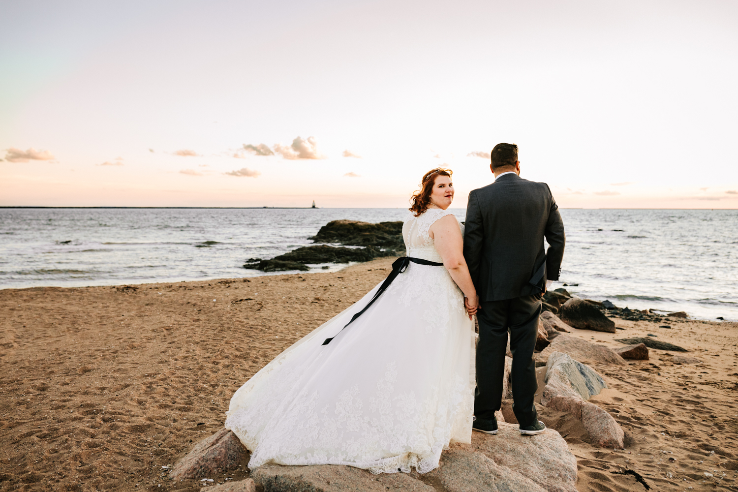 Bride wearing black belt holding hands with groom at sea themed wedding