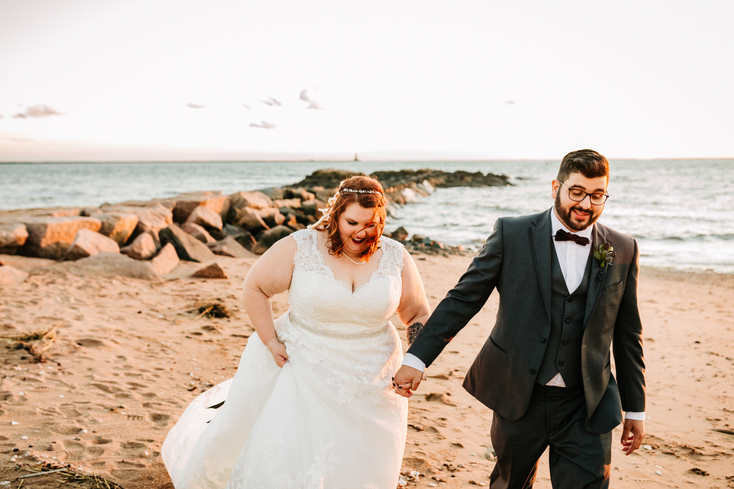 Red haired bride and groom walking along beach on wedding day