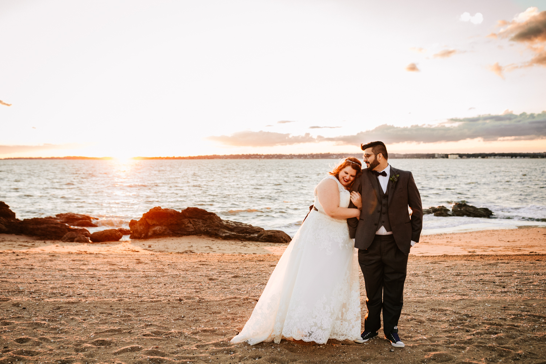 Bride and groom cuddling on beach on ocean themed wedding day