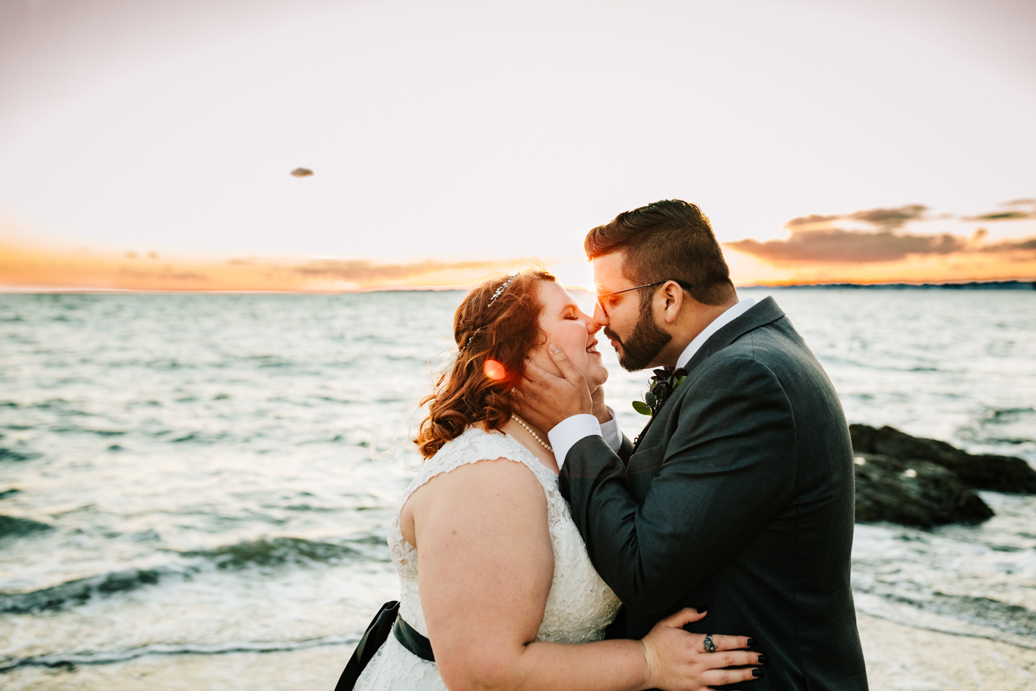 Bride and groom kissing with ocean at sunset