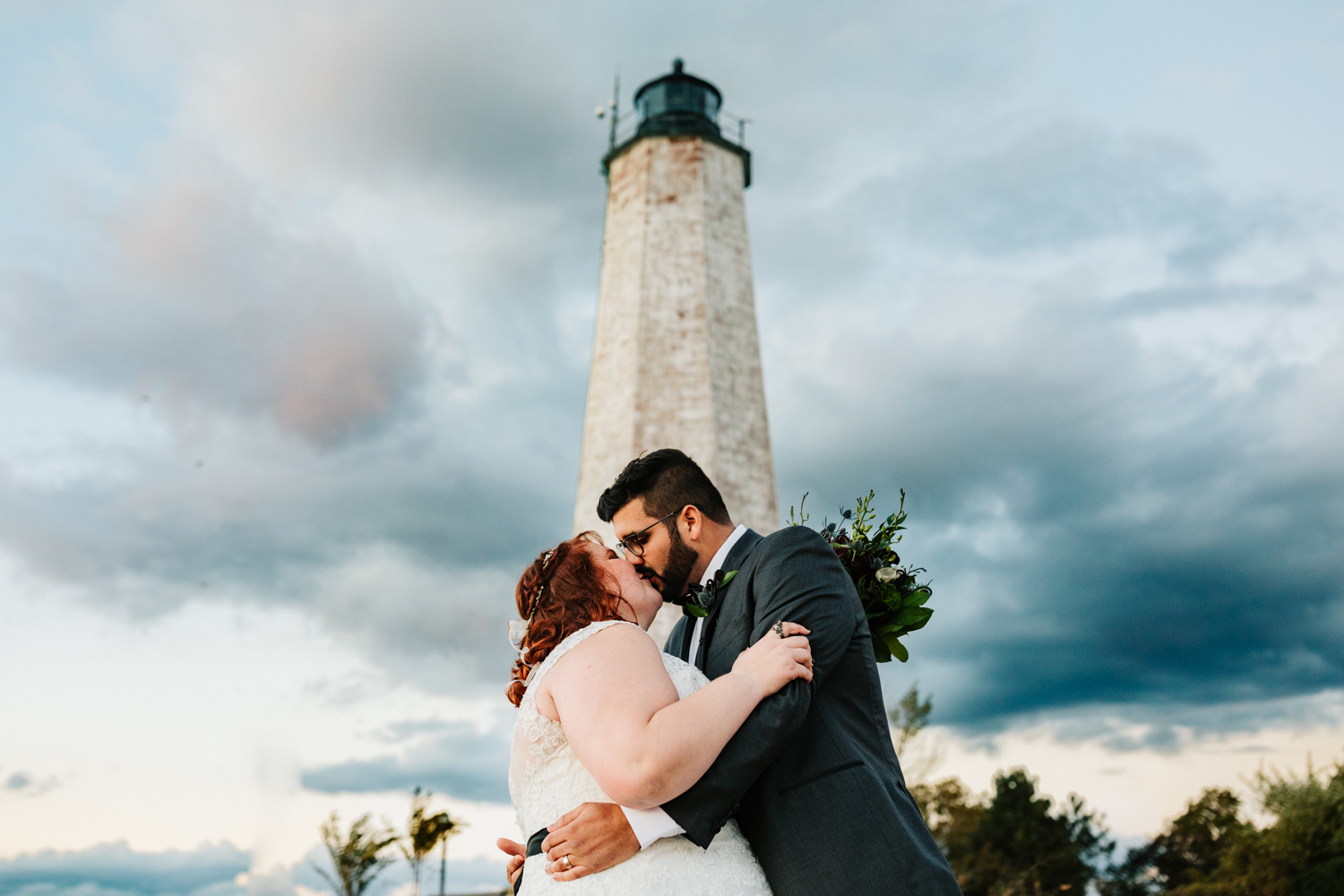 Bride and groom kissing under lighthouse on beach wedding