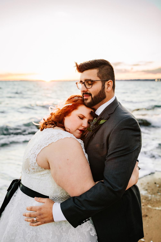 Black belt bride and groom hugging on beach at sunset