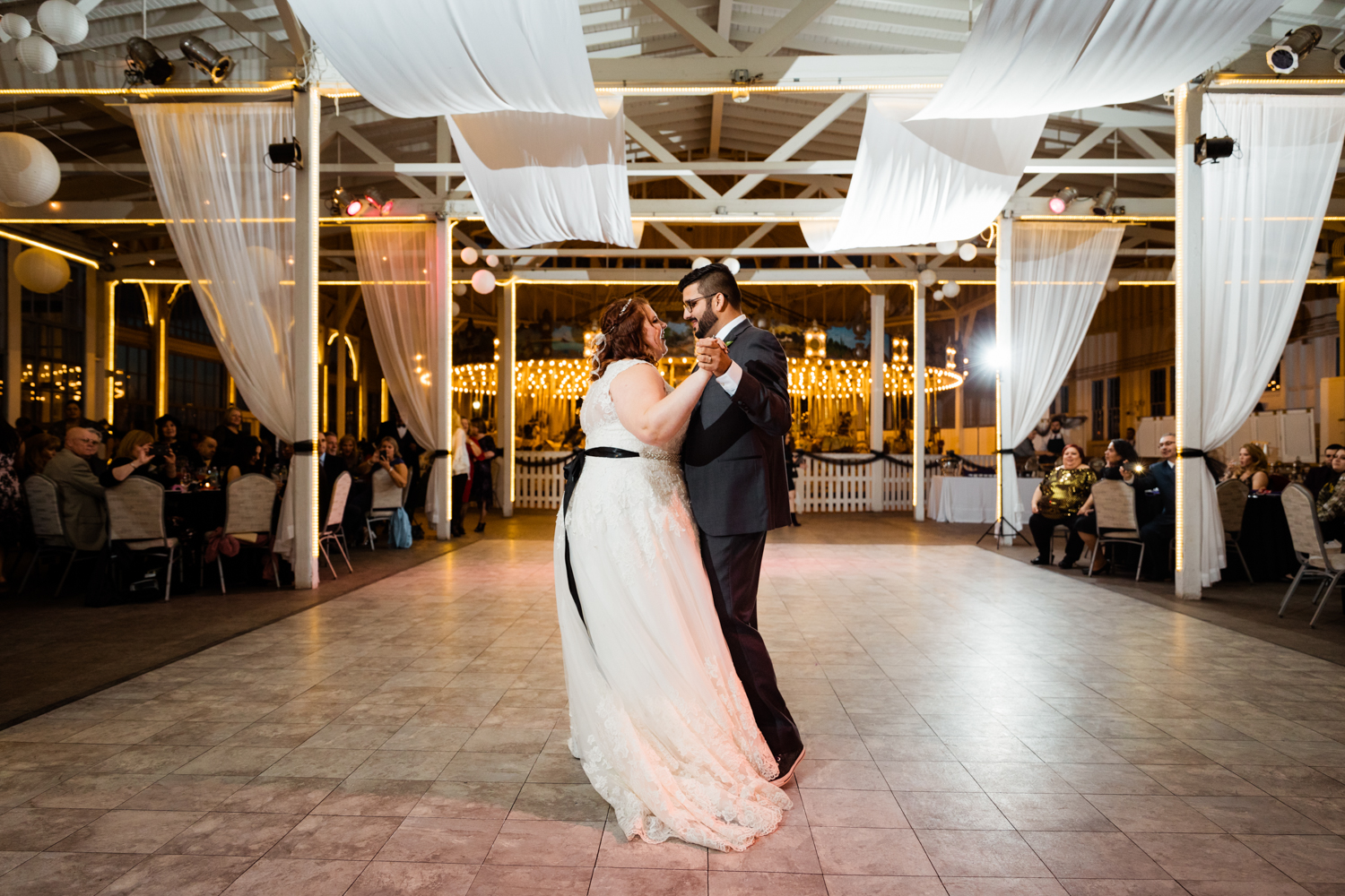 Bride and groom dancing in front of merry-go-round on wedding