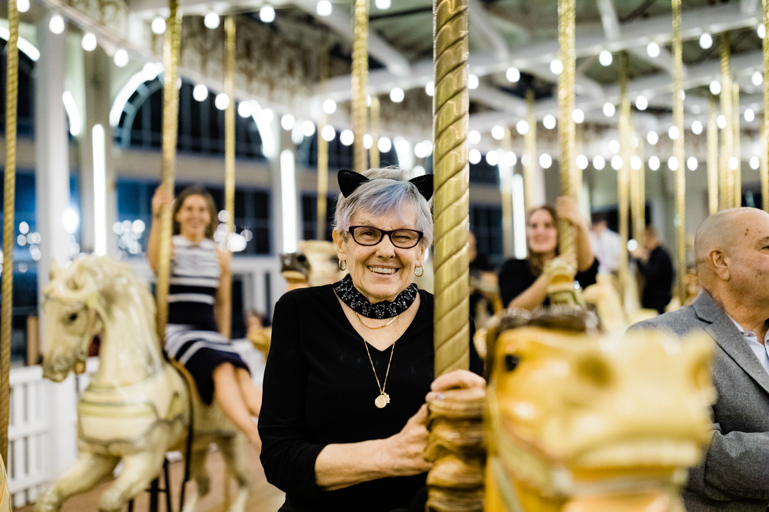 Grandmother smiling on wedding carousel wearing cat ears