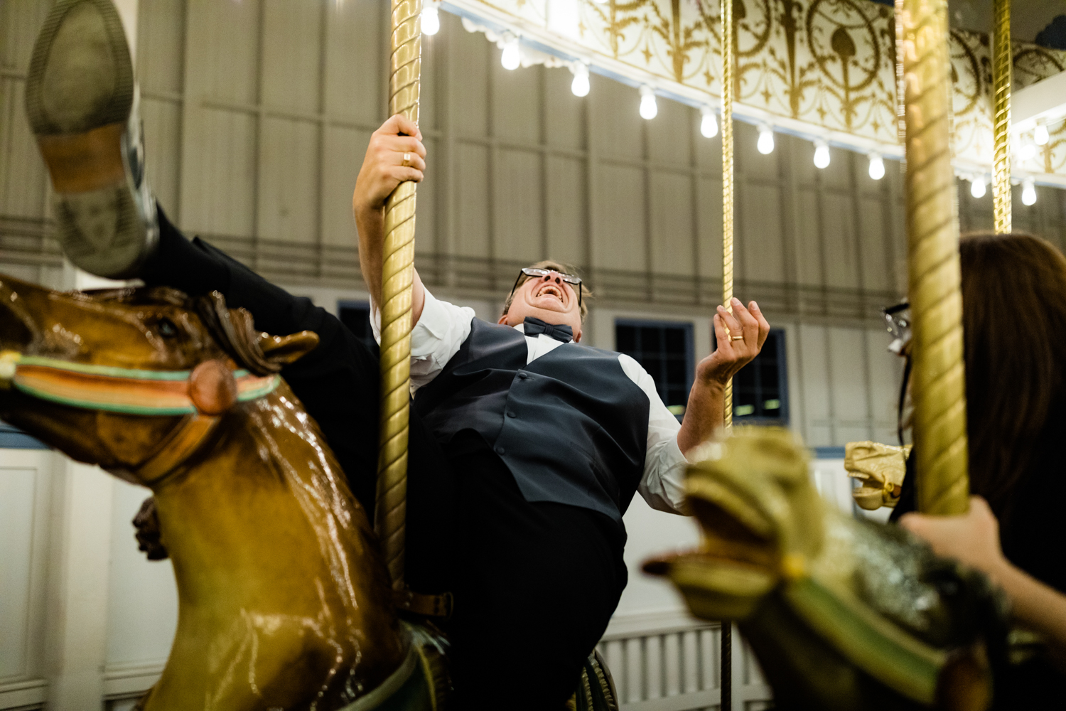 Bride's dad laughing on carousel on wedding day