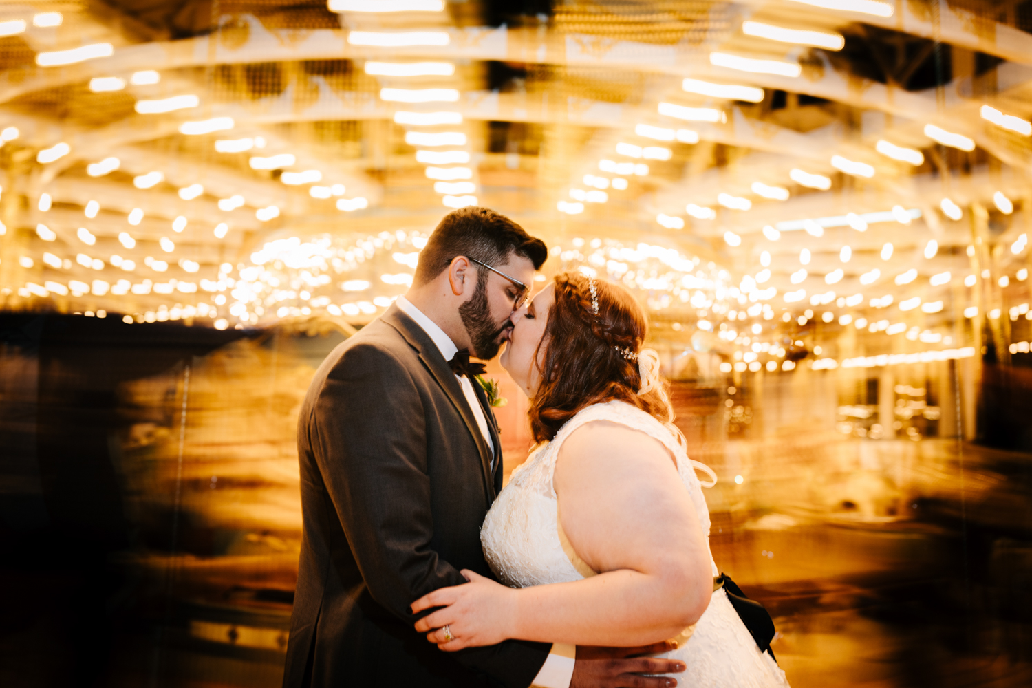 Bride and groom kissing in long exposure photo of carousel