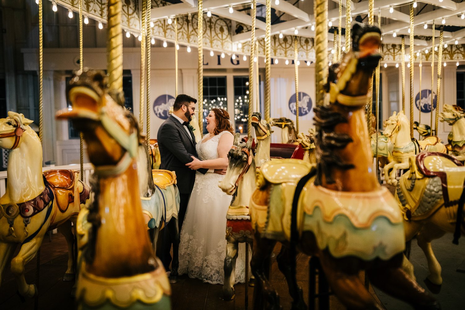 Bride and groom on carousel on wedding day surrounded by merry-go-round horses