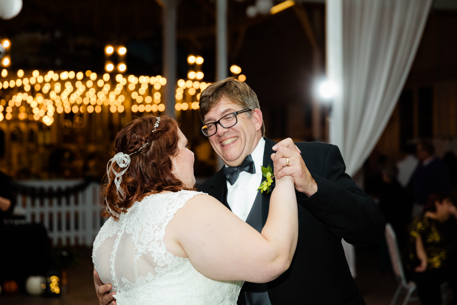 Bride and dad dance in front of carousel lights