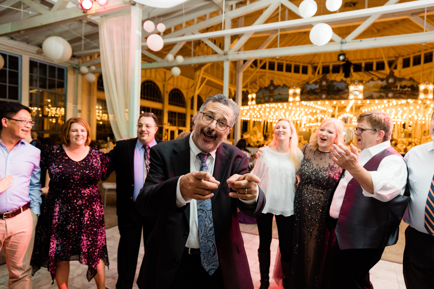 Guests dancing on wedding day with carousel