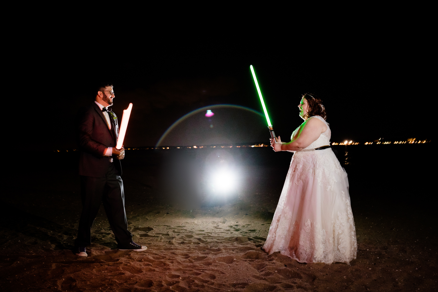 Bride and groom fighting with lightsabers on beach on wedding day