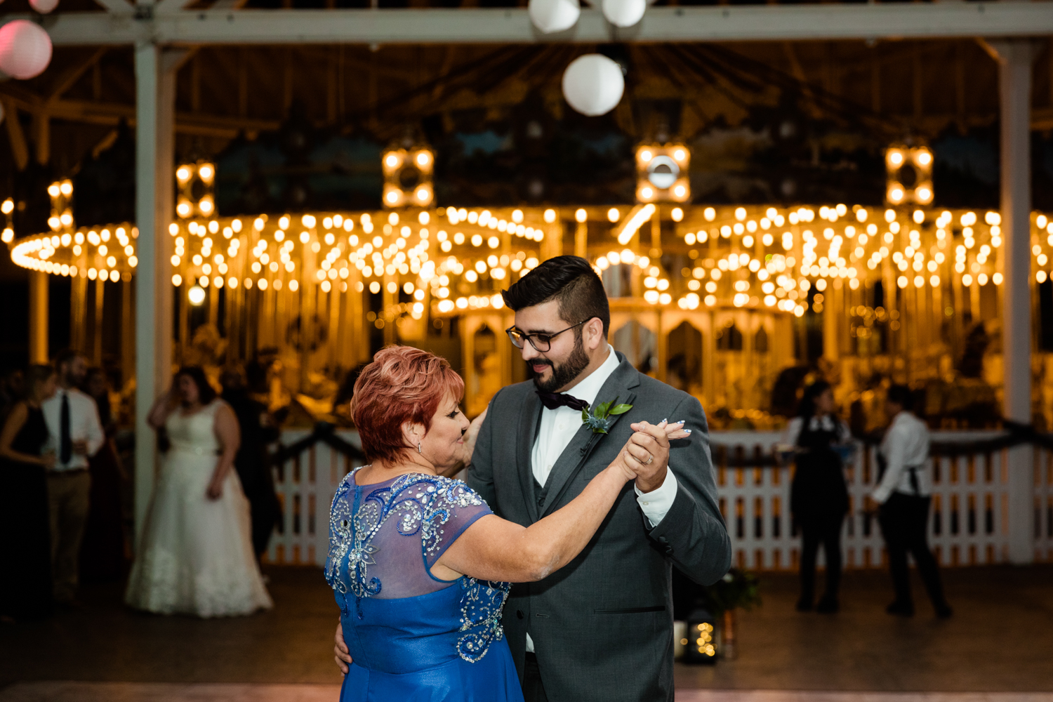 Groom dancing in front of mom in front of carousel
