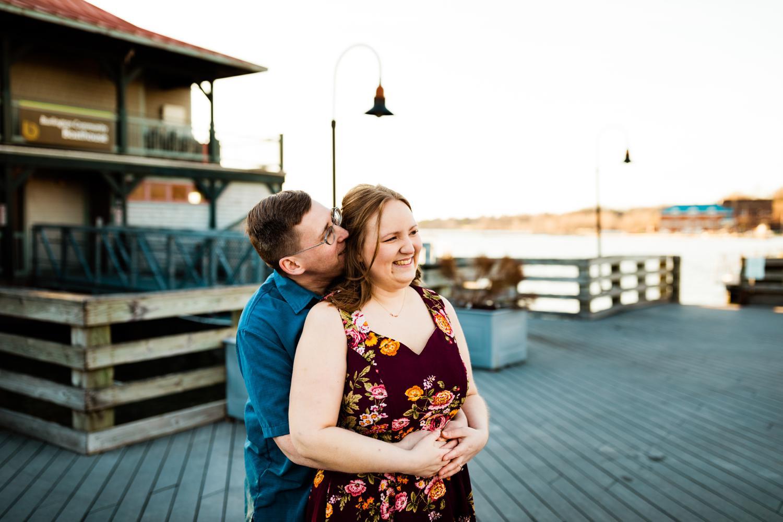 Engaged adventurous couple cuddling on boardwalk