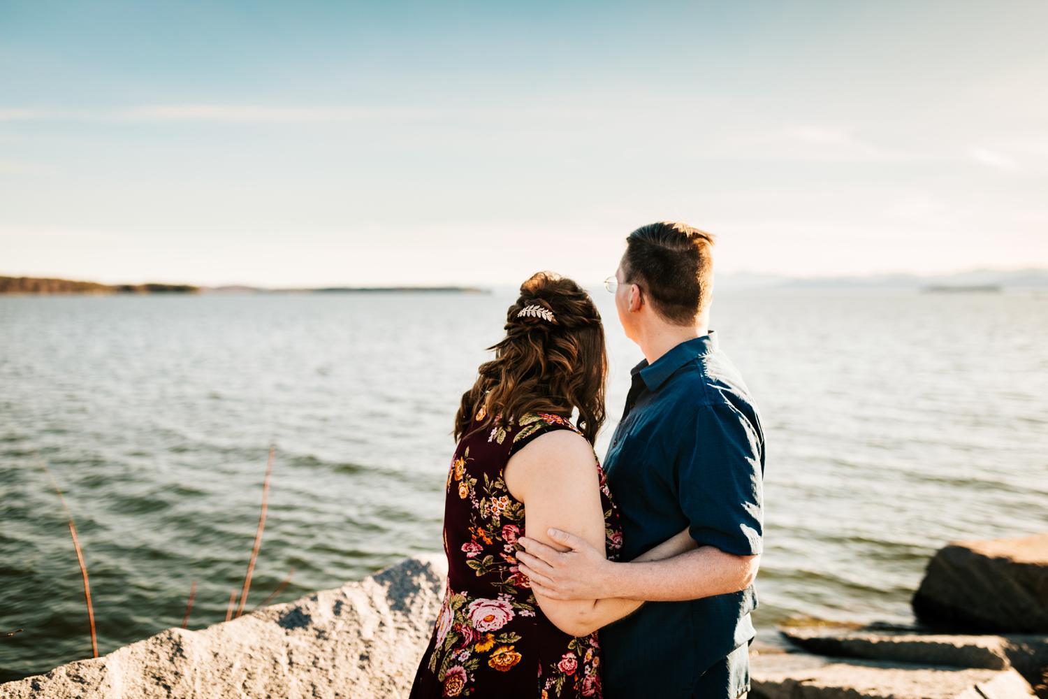 Fun couple looking at mountains and lake for engagement