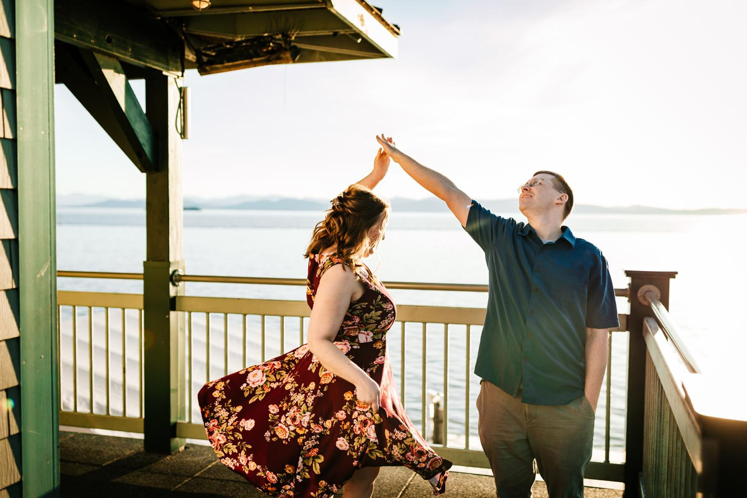 Couple dancing on boardwalk in front of mountains and lake