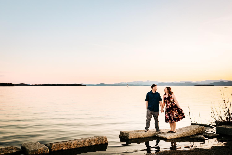 Couple walking along fun lake in front of mountains