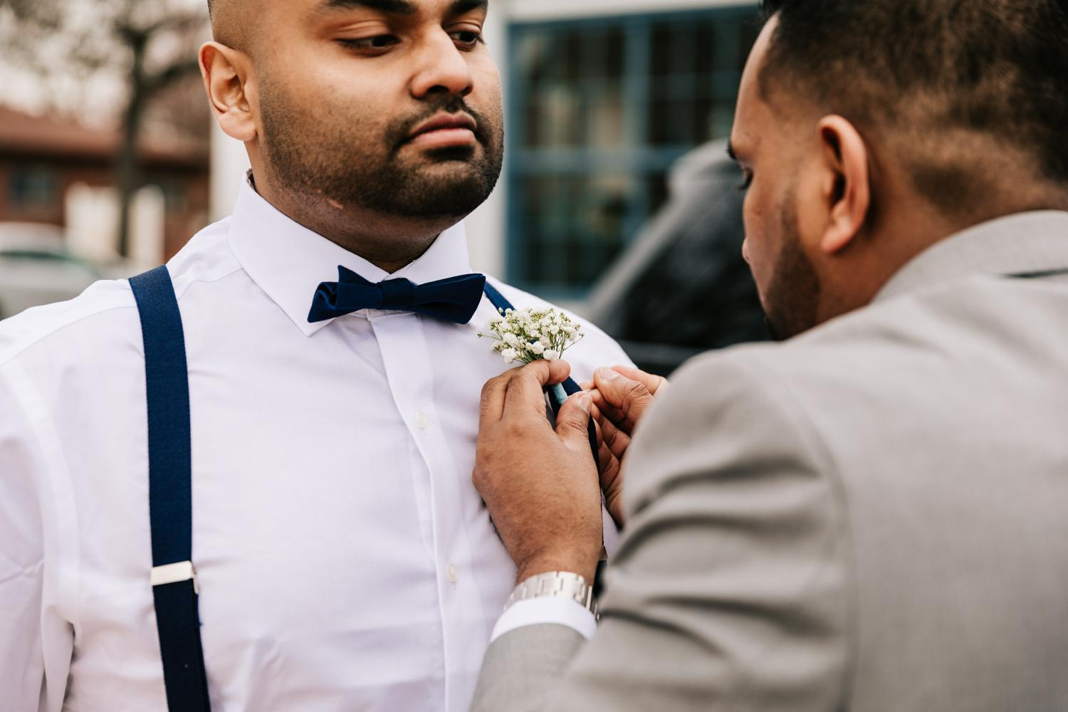 Groom pinning baby's breath flowers on best man