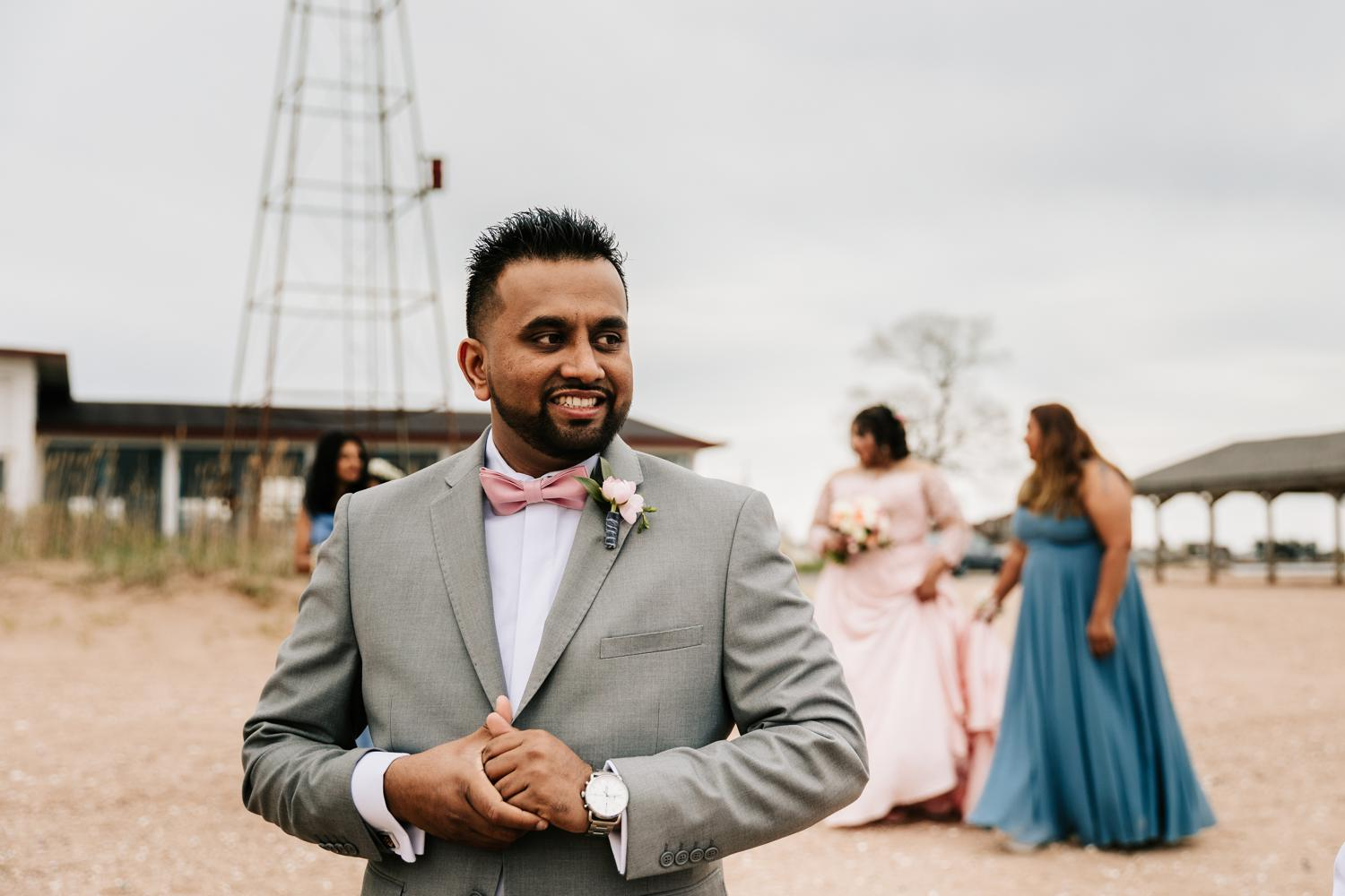 Groom during first look on beach wearing pink bowtie