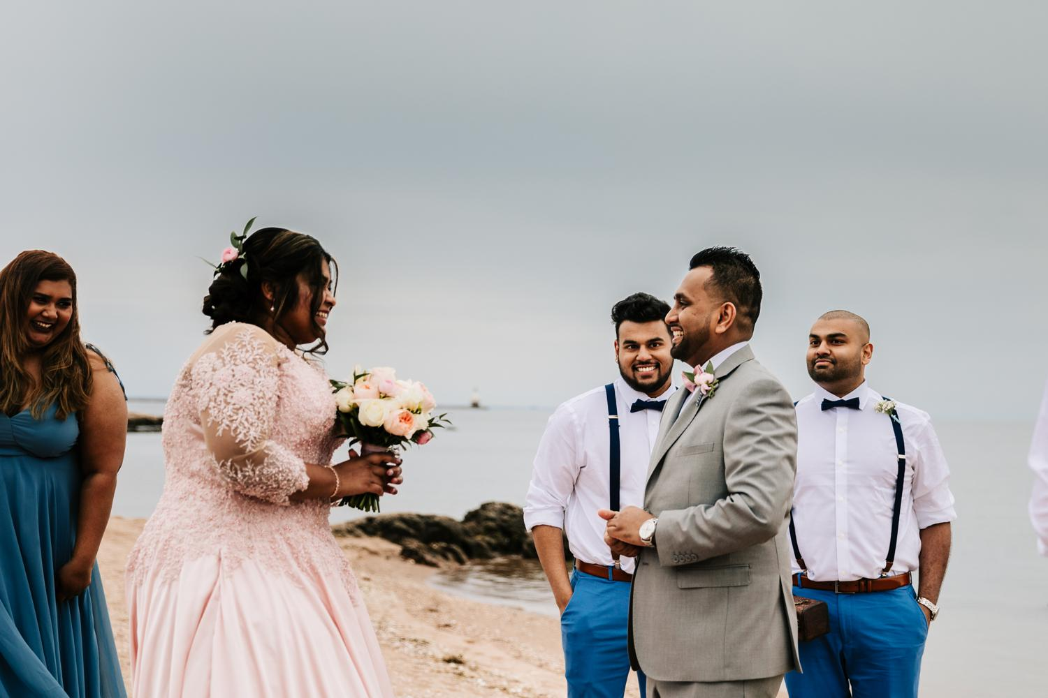 Couple naturally reacting during first look on beach wedding day