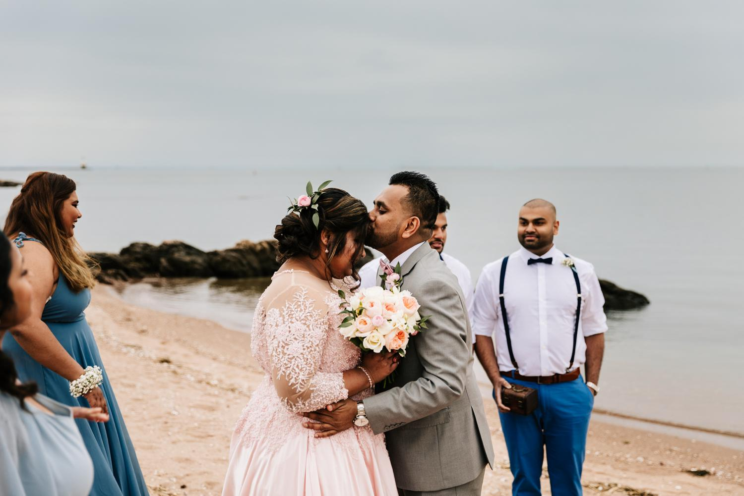 Groom kissing bride's forehead during intimate beach wedding