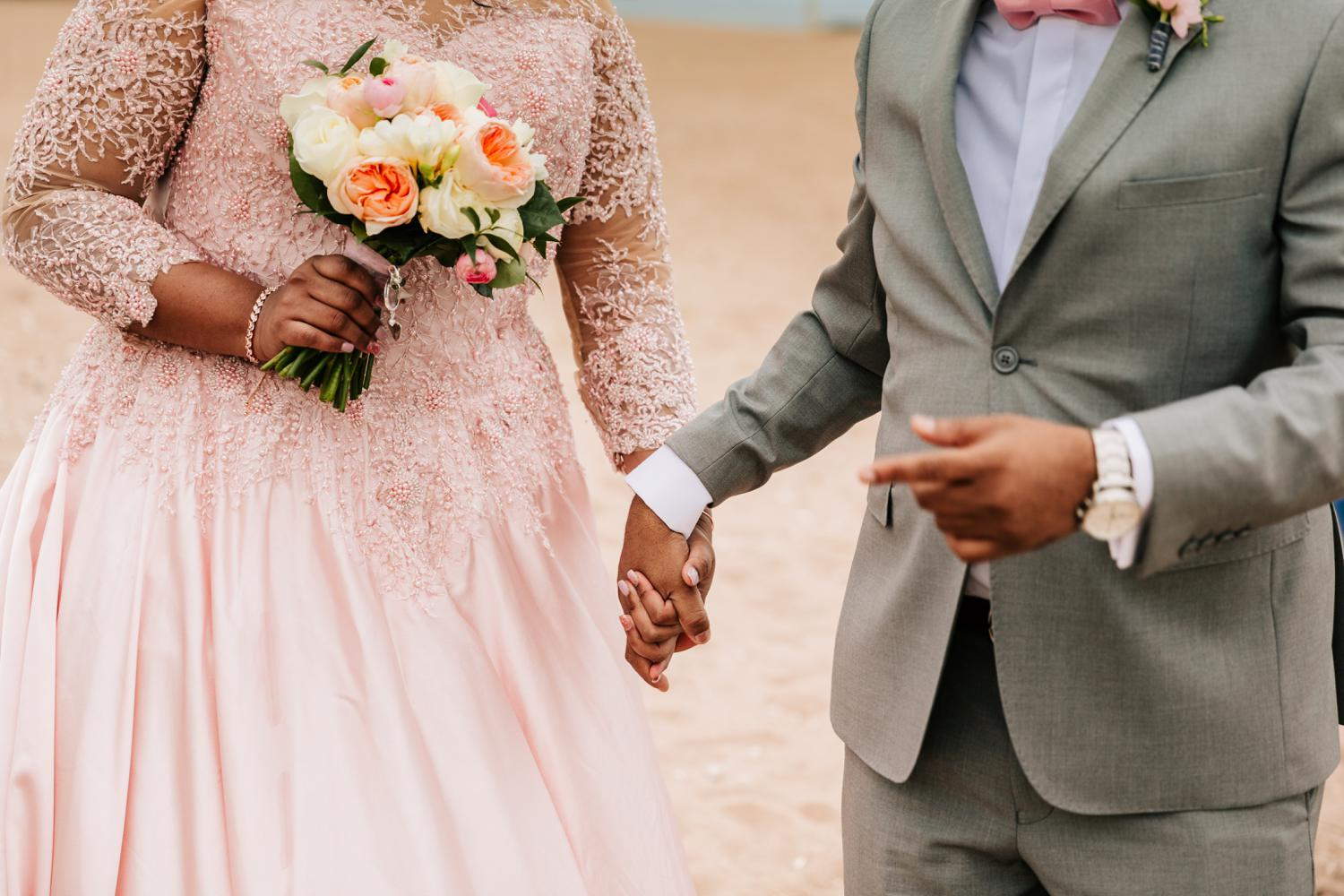 Bride and groom holding hands while bride holds rose bouquet