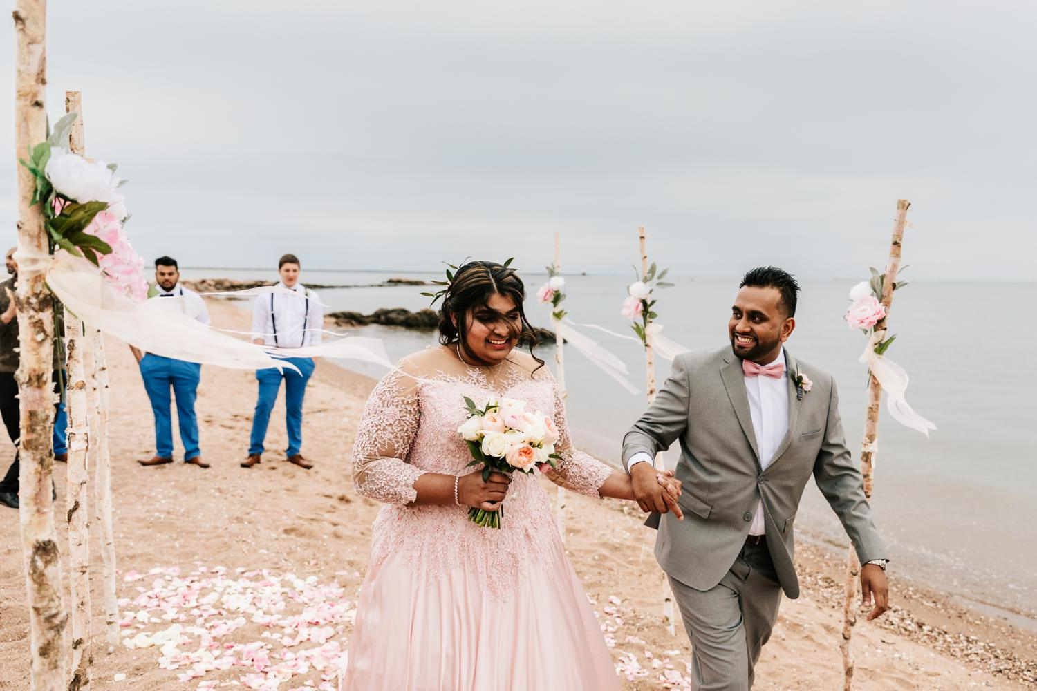 Bride and groom walking down aisle on beach wedding