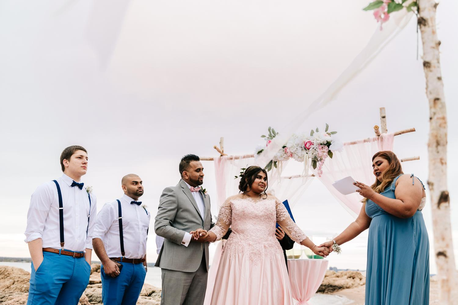 Bridesmaid holding hands with bride and groom while giving speech during beach wedding ceremony