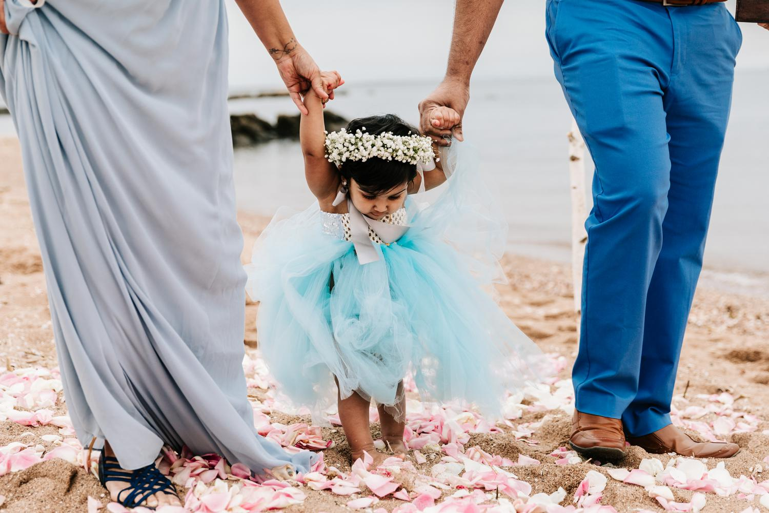 Flower girl baby being walked down aisle
