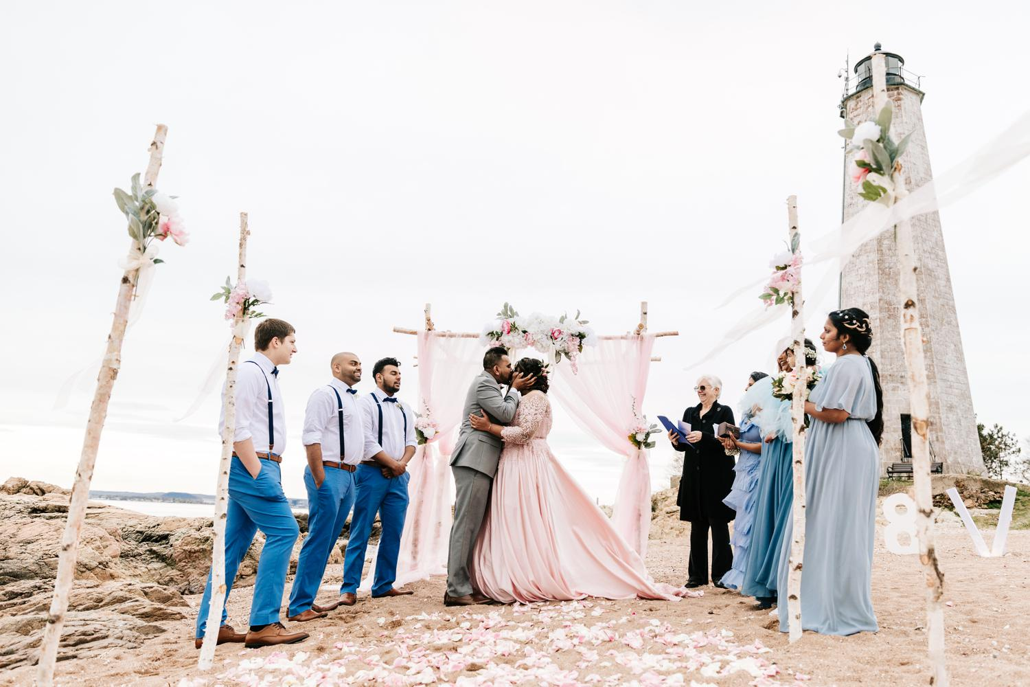 Bride and groom's first kiss on intimate beach wedding ceremony with birch tree and rose decorations