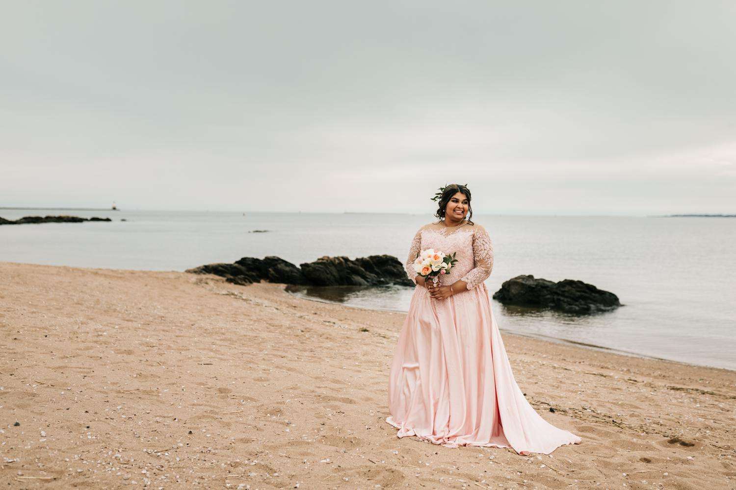 Bride in pink wedding dress on beach at sunset