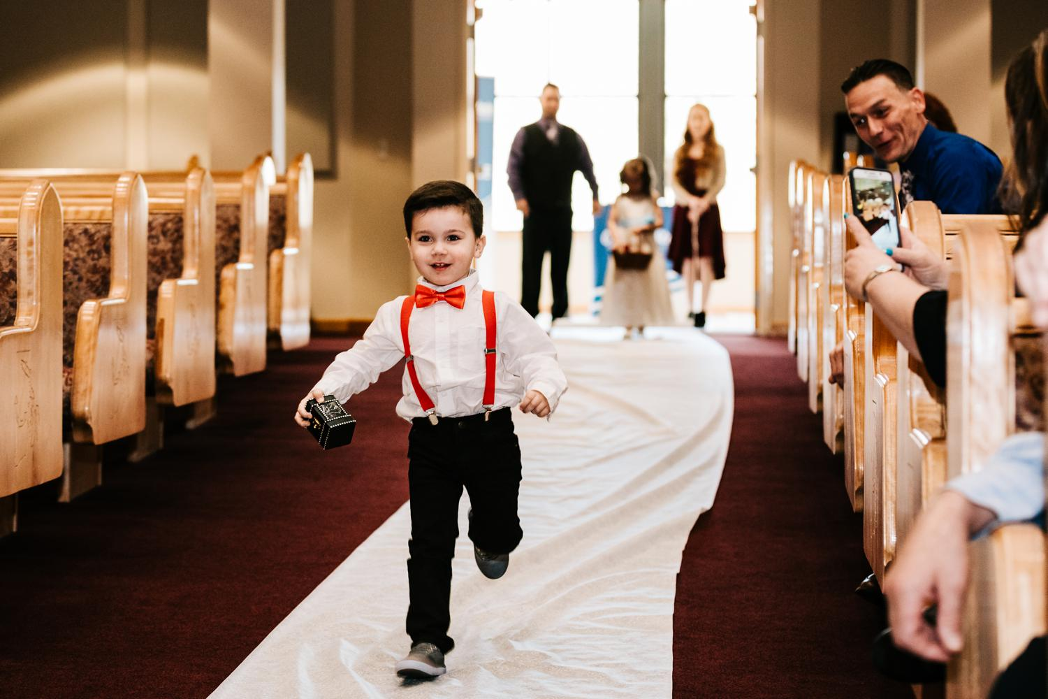 ringbearer running down aisle with ring in tiny chest