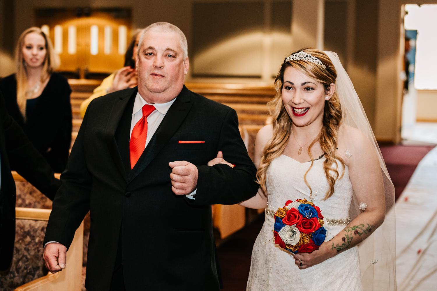 smiling bride in tiara being walked down aisle by father