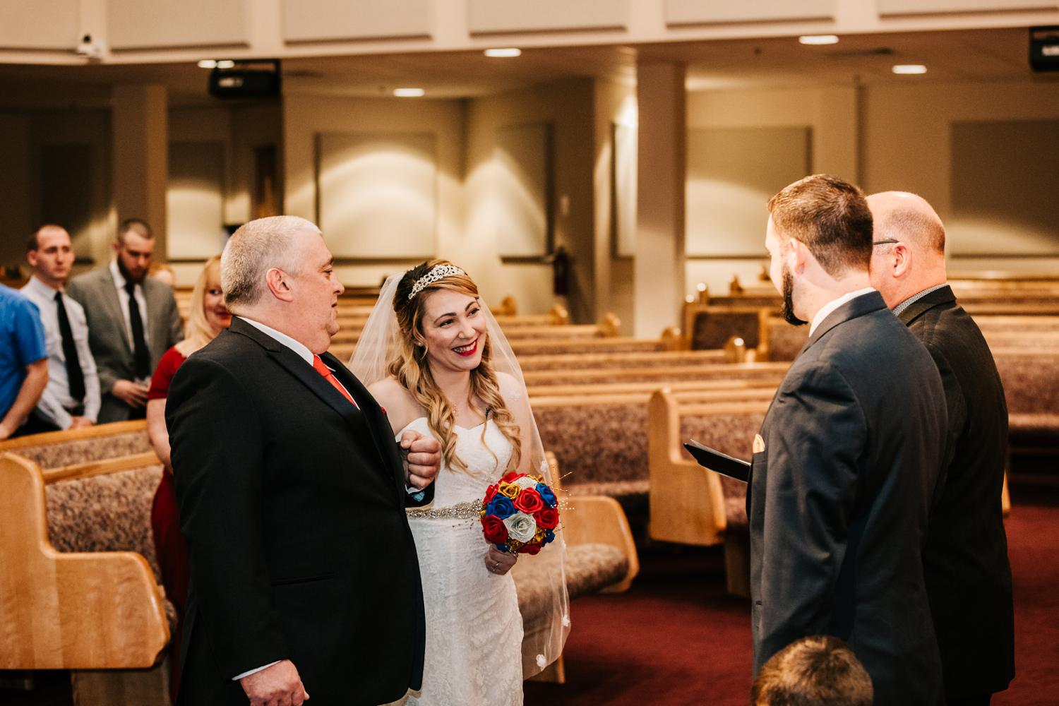 Father giving away bride looking at groom