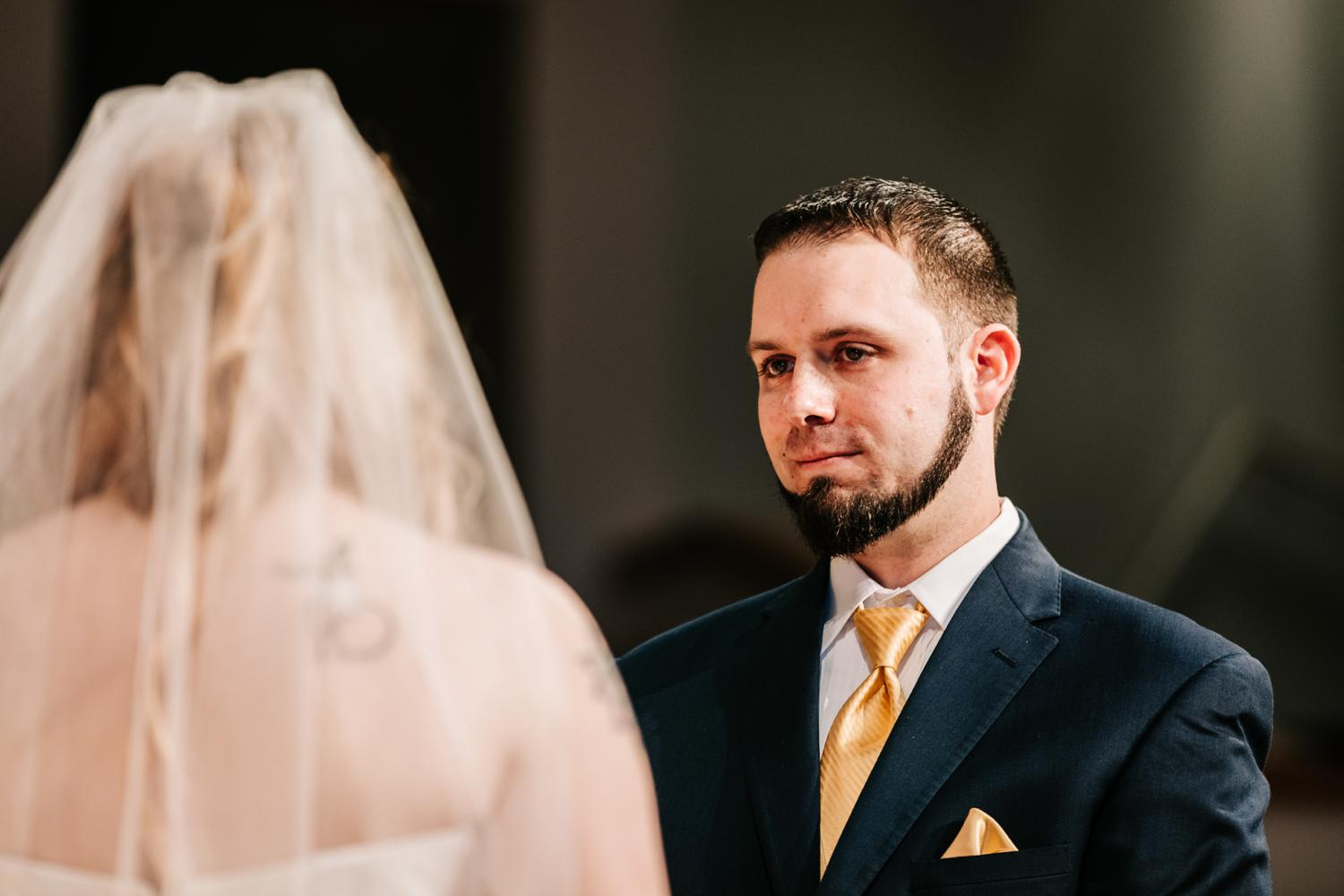 Groom's expression as he looks at bride
